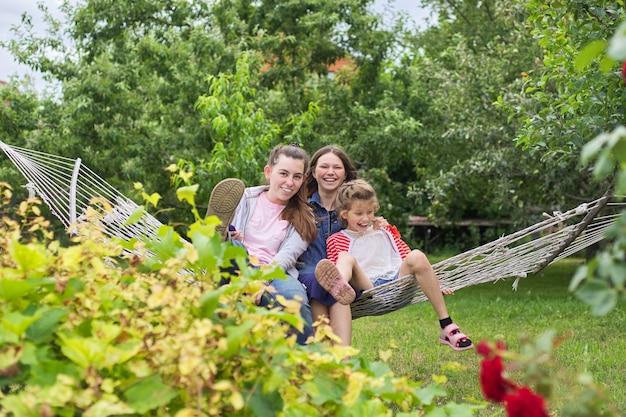 3人の10代の少女と庭のハンモックで笑って楽しんでいる子供