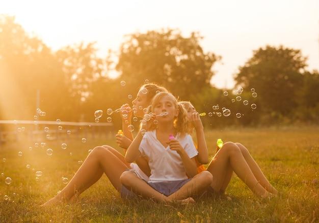 세 명의 십대 소녀들이 공원에서 즐거운 시간을 보내고 있습니다. 두 친구 야외입니다. 거품을하는 여름 사람들