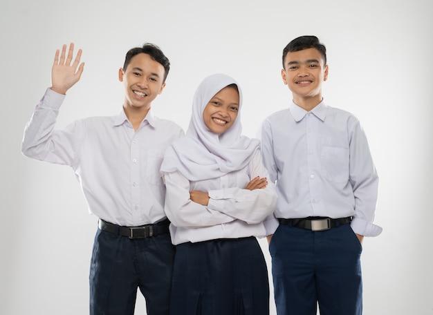 立っているときに挨拶のジェスチャーで笑っている中学生の制服を着た3人のティーンエイジャー