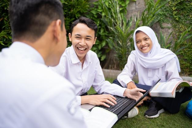 制服を着た3人のティーンエイジャーが一緒に勉強し、座ってノートパソコンと本を使ってチャットします...