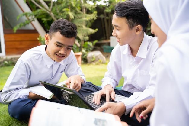 교복을 입은 세 청소년이 앉아있는 동안 노트북을 사용하여 수업을 논의하면서 함께 공부합니다.