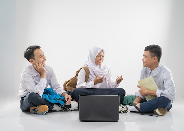 Three teenagers in junior high school uniforms sitting on the floor studying together and chatting w...