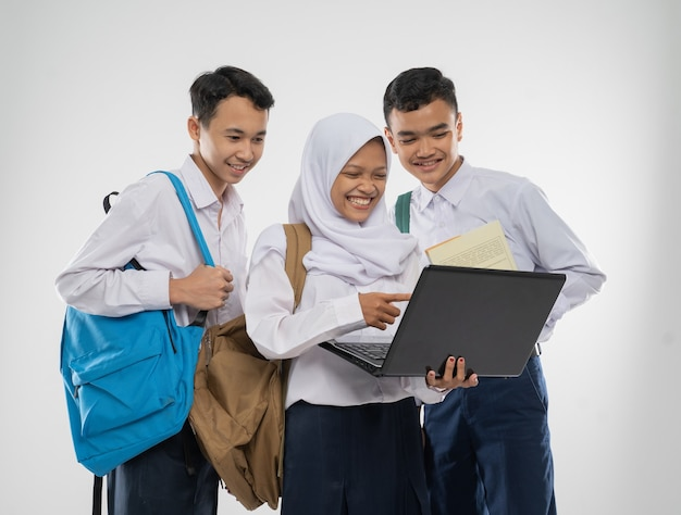 Three teenagers in junior high school uniforms smiling using a laptop computer together while carryi...