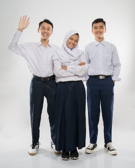 Three teenagers in junior high school uniforms stand smiling at the camera while greeting with a han...