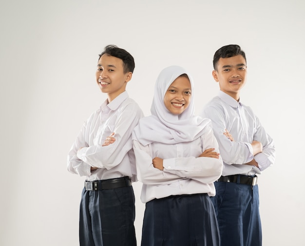 Three teenagers in junior high school uniforms stand smiling with crossed hands