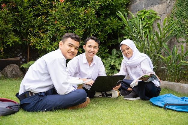 3人のティーンエイジャーがラップトップを使用して一緒に勉強している制服のカメラに微笑む