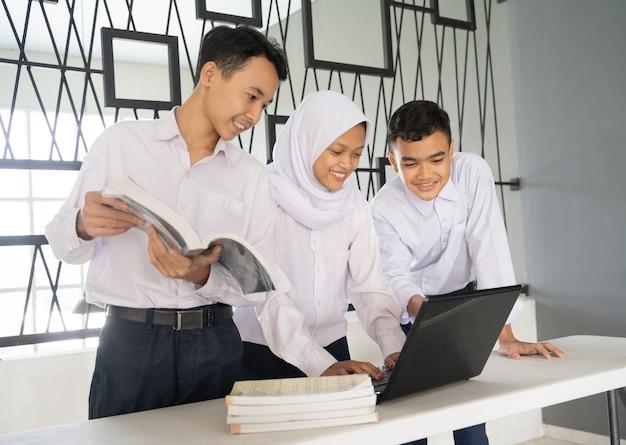 노트북과 여러 권의 책을 사용하여 교복을 입고 함께 공부하는 세 청소년