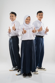 親指を立てて立っている中学生の制服を着た3人のティーンエイジャー