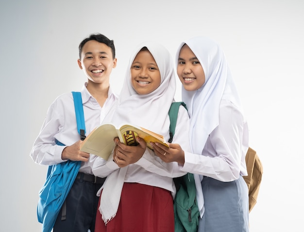 Three teenagers wearing school uniforms smile at the camera with a backpack and a book