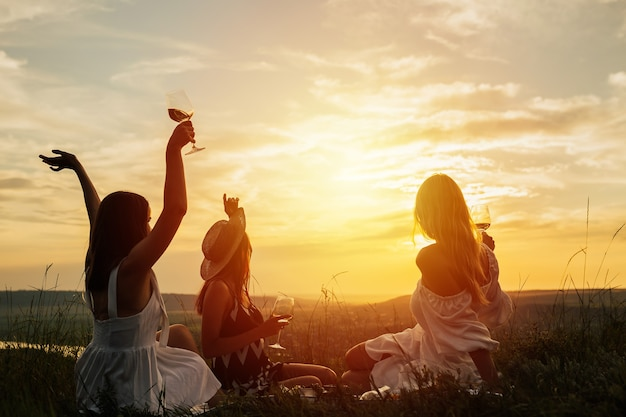 Three tender girlfriends on vacation, sit turned towards the colourful sunset sky and enjoying beauty of nature, picnic on a field at sunset