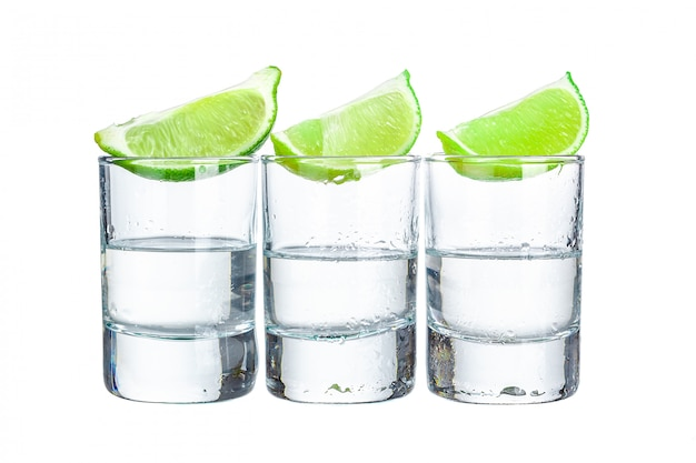 Three  tequila shots with lime  on white background