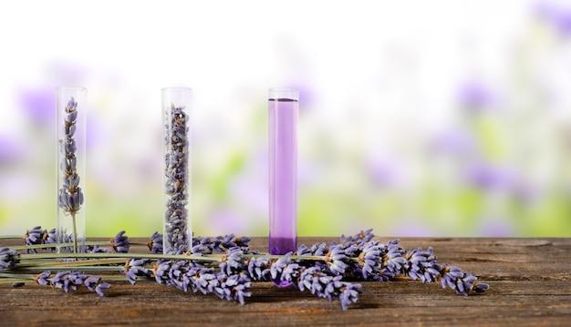 ラベンダーの花とアロマエッセンスを木製にラベンダーの花で飾った3本の試験管。自然のぼやけた背景。
