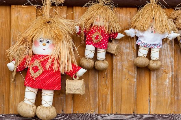 Три текстильные куклы в красных и белых футболках с небольшими деревянными коробками.