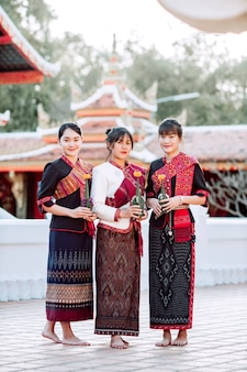 Three thai girl in the phu thai tribe standing in the thai temple area