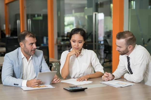 Three thoughtful marketing analysts working with diagrams