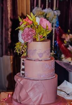 マスチックな牡丹で飾られた3層のピンクのウエディングケーキ。結婚式のコンセプト。