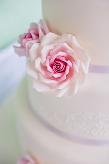 Three tiered wedding cake with pink roses made of mastic stands on the table