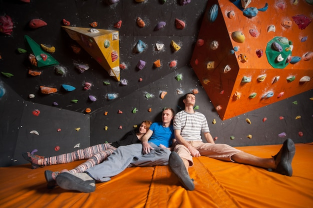 Three tired climbers sitting near rock wall indoors