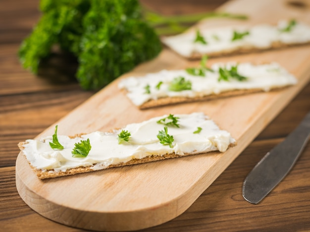 まな板の上にクリームチーズを添えたトースト3枚。ベジタリアンスナック。クリームチーズとパンの野菜。