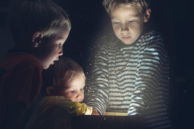 きらめく光とキラキラ光る金色のギフトボックスに手を伸ばす3人の幼児の子供たち。