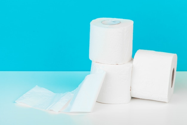 Three toilet paper rolls isolated on white table with blue