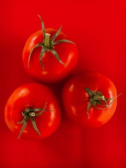 빨간색 배경에 3 토마토입니다.