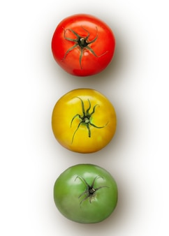 Three tomatoes in a row isolated on white background. red, green and yellow tomatos looks like traffic lights. flat lay view. close up