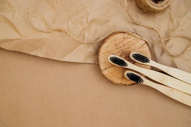 천연 대나무로 만든 칫솔 3개가 갈색 크라프트지의 배경에 나무 조각 위에 놓여 있습니다. 지속 가능한 라이프스타일과 플라스틱 없는 컨셉, 욕실 필수품.