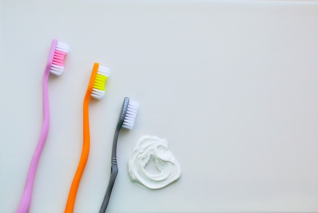 Three toothbrushes on a white background and white toothpaste