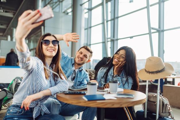 세 명의 관광객이 공항에서 전화로 셀카를 만듭니다. 수하물이있는 승객은 공항 터미널에서 비행을 기대합니다