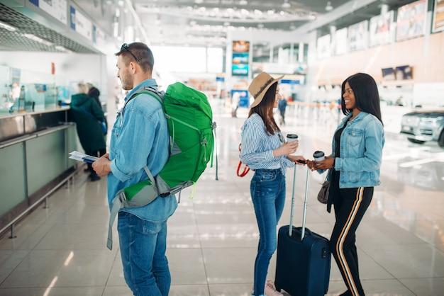 Трое туристов с багажом получают посадочный талон в аэропорту. пассажиры с багажом в аэровокзале