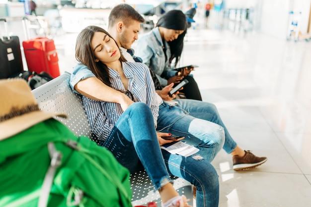 空港で出発が遅れるのを待っている荷物を持つ3人の観光客。