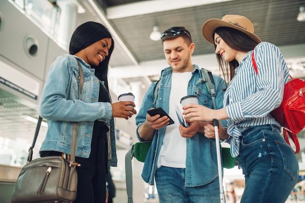 Трое туристов с багажом ждут вылета и пьют кофе в аэропорту, мужчина-путешественник по мобильному телефону.