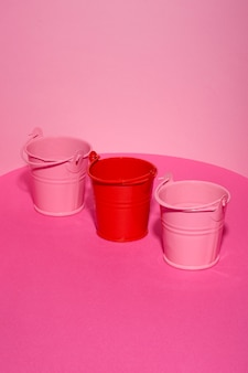 Три игрушечные ведра на розовом