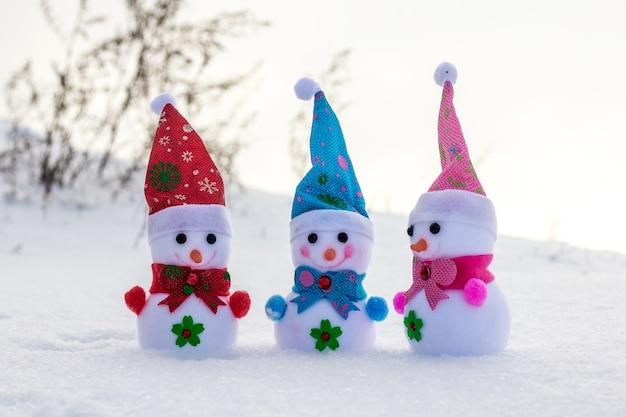 Три игрушечных снеговика в снегу. веселая дружная компания_
