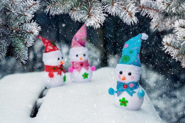 Три игрушечных снеговика в снегу под елью во время снегопада. новогодняя и рождественская открытка