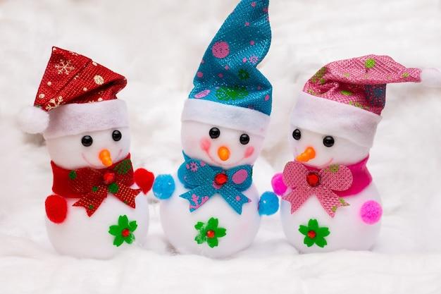 Три игрушечных снеговика на белом снегу