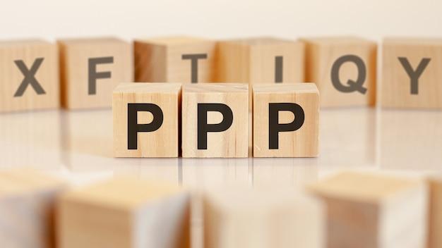 明るい表面のテーブルにpppの文字が付いた3つのおもちゃの木のブロック