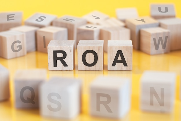 Three toy wooden blocks with letters roa on a table with light yellow surface. roa - short for return on assets