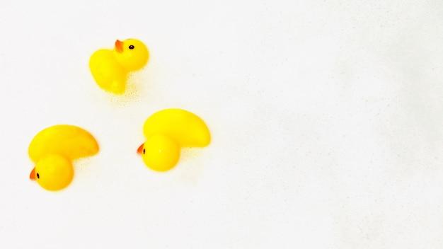 거품에 오리 모양의 세 가지 장난감. 물 거품에 떠 있는 욕조에 있는 노란색 고무 오리의 높은 시야각. 비누 거품에 노란색 고무 오리, 아이들을 위한 재미. 복사 공간