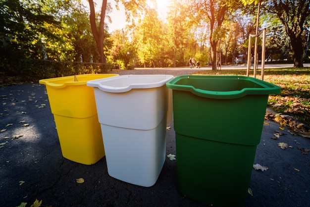 Three trash containers in different color