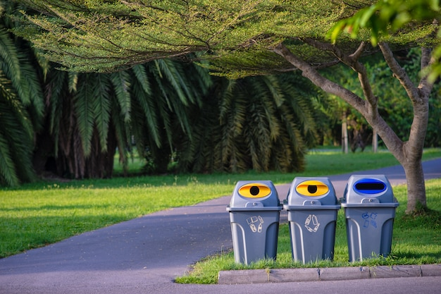 Three trashcans in a park with green tree and plants in public park