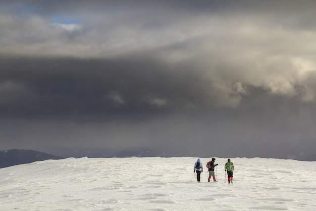 Three travelers tourist hikers in bright clothing on snowy field
