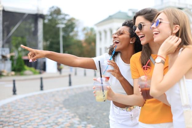 Три модные крутые хипстерские девушки, друзья пьют коктейль на фоне городского города.