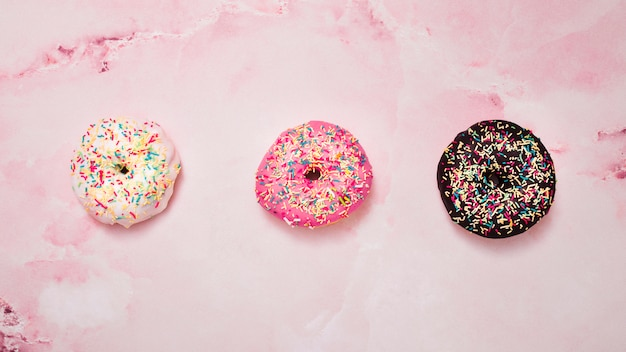 Three type of white; pink and chocolate donuts with sprinkles against pink background