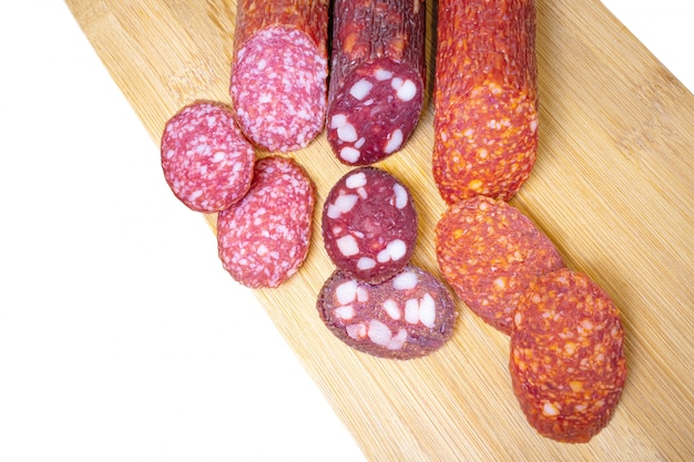 Three types of appetizing uncooked smoked sausage on a white background.