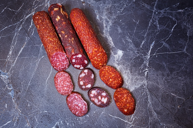 Three types of appetizing uncooked smoked sausages on a dark marble background. top view.