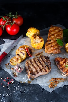Three types of grilled meats with vegetables and spices on paper