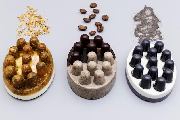 Три вида мыла ручной работы с календулой, натуральным кофе и глиной на сером фоне. натуральная органическая домашняя косметика для ухода за кожей. скраб для кожи. антицеллюлитные процедуры.