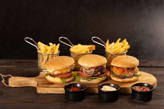 Три вида сочных котлет из свинины, говядины и курицы с картофелем фри и различными соусами прекрасно сохраняются на темном деревянном столе.